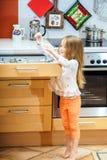 Little girl getting tableware before dinner. Little girl getting tableware from table case before dinner Stock Photos