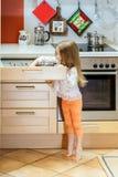 Little girl getting tableware before dinner. Little girl getting tableware from table case before dinner Royalty Free Stock Image
