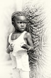 Little girl from Ghana eats something near a tree Royalty Free Stock Images