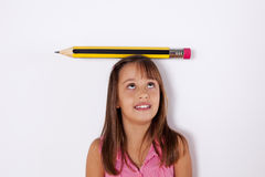 Little girl with a giant pencil over her head. Little girl next to the wall with a giant pencil over her head Stock Image