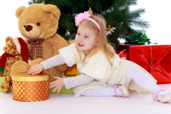 Little girl with gift. Adorable little blonde girl is sitting near the Christmas tree. Girl stretches hands to a large round box which is a gift. Beside her sits Royalty Free Stock Photo