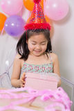 Little girl with gift box at her birthday party Stock Photo