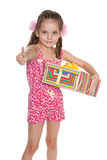 Little girl with a gift box holds her thumb up Stock Image