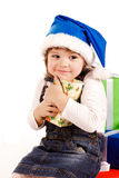 Little girl with gift boxes in Santa's hat Royalty Free Stock Images