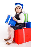 Little girl with gift boxes in Santa's hat Royalty Free Stock Photos