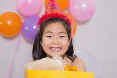 Little girl with gift at her birthday party Royalty Free Stock Photos