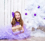 Little girl with a gift   near Christmas tree Royalty Free Stock Photography