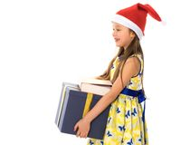 A little girl with a gift in a Santa Claus hat. stock photography