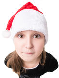 Little girl with a gift in a Santa hat Stock Images