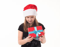 Little girl with a gift in a Santa hat Royalty Free Stock Image