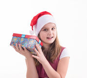 Little girl with a gift in a Santa hat. Little girl with a gift in a red Santa hat stock images