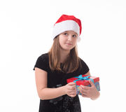 Little girl with a gift in a Santa hat. Girl teenager with a gift in a Santa hat Royalty Free Stock Images