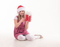 Little girl with a gift in a Santa hat. Girl teenager with a gift in a Santa hat Stock Images