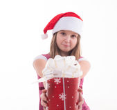 Little girl with a gift in a Santa hat. Girl teenager with a gift in a Santa hat Royalty Free Stock Photography