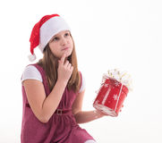 Little girl with a gift in a Santa hat. Girl teenager with a gift in a Santa hat Stock Image
