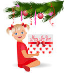 Little girl with a gift under the Christmas tree. Royalty Free Stock Image