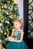 Little girl with gift wearing dress and standing near Christmas tree. Concept of presents, childhood and winter holidays Stock Photography