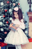 Little girl with gifts by the Christmas Tree Stock Photos