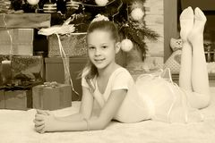 Little girl with gifts by the Christmas Tree Stock Photo