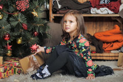 Little girl with gifts near a Christmas tree Stock Images