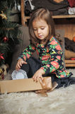 Little girl with gifts near a Christmas tree Stock Photo