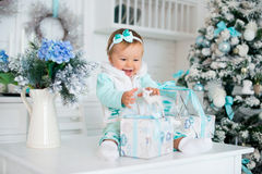 A little girl with gifts and a toy deer. Christmas holidays. stock photo