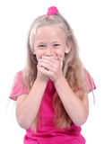 Little girl giggling. Portrait of a cute little Caucasian girl with funny facial expression giggling with her hands in front of her mouth. Image isolated on Royalty Free Stock Photo