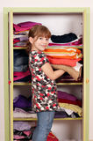 Little girl girl agrees clothes. In a closet stock images