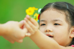 Little girl give flower to mother. Cute Asian little girl gives flower to her mother Royalty Free Stock Photography