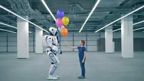 Little girl gives balloons to a droid, side view. School kid, education, science class concept. A girl gives many balloons to a robot stock video footage