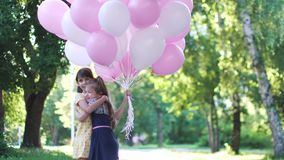 A little girl gives a bouquet of balloons to your girlfriend. Two little sisters in summer Park. Children run through the Park with a huge bunch of colorful stock footage