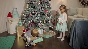 Two small children open gifts near Christmas tree. A little girl gives a Christmas gift to a little boy near a decorated Christmas tree. New years eve stock footage
