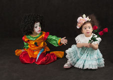 Little girl gives flowers to boy - clown, african Stock Images