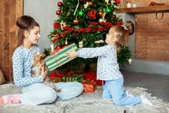 The little girl gives a gift to his sister. The concept of Chris. Tmas and New Year Royalty Free Stock Photography