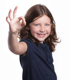 Little Girl Gives O.K. Sign. A cute little girl with curly hair and freckles gives an O.K. sign while smiling Stock Image