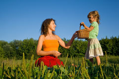 Little Girl gives Young Women basket on glade royalty free stock photo