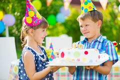 Little girl giving a birthday cake to a friend Royalty Free Stock Images