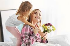 Little girl giving bouquet of beautiful flowers to her mother. Mother`s day concept Stock Image