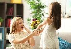 Little girl giving bouquet of beautiful flowers to her mother. Mother`s day concept Stock Photography