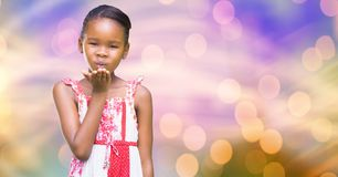 Little girl giving flying kiss over blur background Royalty Free Stock Photo