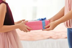 Little girl giving gift box to her mom indoors. Mother`s day celebration Stock Photography
