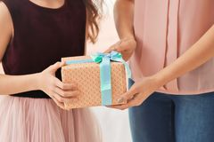 Little girl giving gift box to her mom indoors. Mother`s day celebration Stock Images