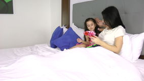 Little girl giving a gift to her mother in the bedroom stock footage