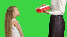 Little girl giving a gift to her mother and kissing on a green screen, chroma key stock video footage