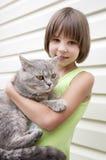 Little girl giving her gray kitten Royalty Free Stock Photo