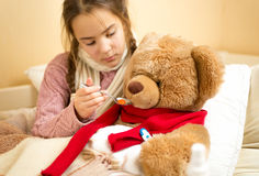 Little girl giving medicines to teddy bear Royalty Free Stock Photo