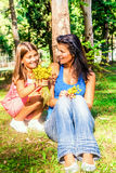 Little girl is giving mum flowers. In the park stock photography