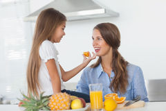 Little girl giving an orange segment to her mother Stock Photo