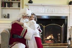 Little girl giving Santa Clause a hug Stock Photos
