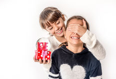 Little girl giving surprise love gift to her friend with white b Stock Photos